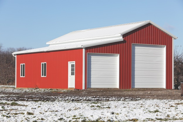 """In early winter, construction is almost complete on this brand new, bright red and white corrugated metal warehouse/vehicle storage building on a rural road at the edge of a large apple orchard in western New York state, USA. Apple trees can be seen in the background.-- -- --Related images:"""